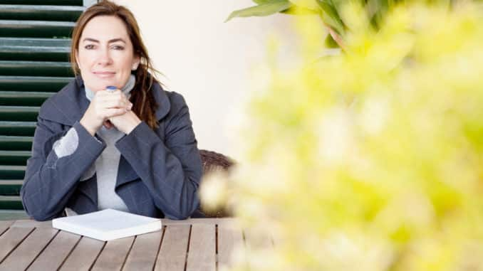 Frau im Herbst auf der Terrasse