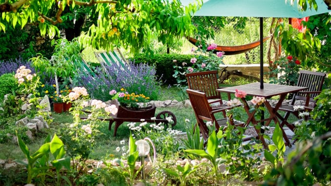 Wunderschöner Garten mit Holztisch und Stühlen