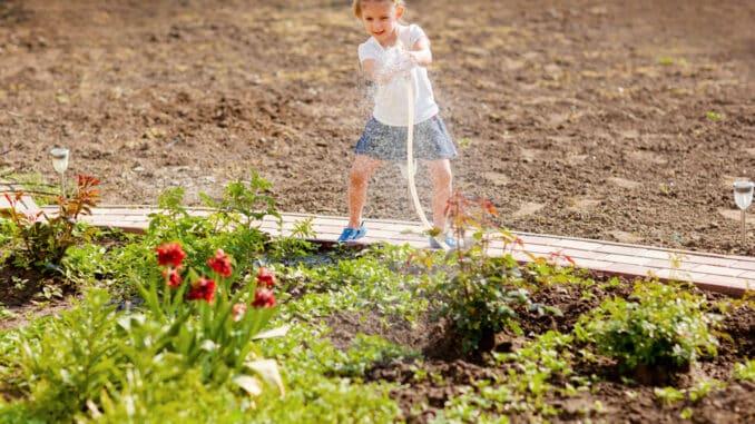 Mädchen gießt Blumen mit Brunnenwasser